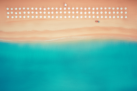 Aerial top view on the beach. Umbrellas, sand and sea waves Archivio Fotografico