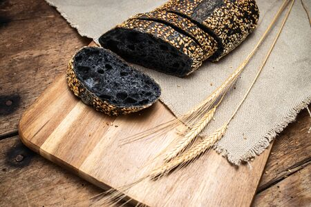 Homemade sourdough black bread baguette on vintage towel and old wooden table