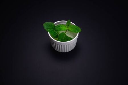 Fresh mint leaves in plate isolated on black background.