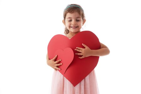 Happy little girl holds heart shaped cards in her hands. Feeling love concept