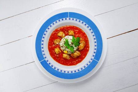 Spicy barley risotto with chicken and  tomato sauce on white background.