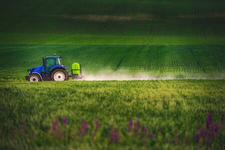 Farming tractor plowing and spraying on field. Stok Fotoğraf