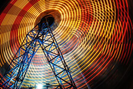 Ferris Wheel at county fair at night, motion blurred.