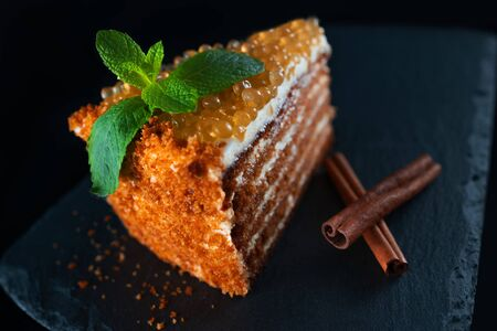 Honey cake with golden pearls and mint leaf and cinnamon on stone plate isolated on black background 스톡 콘텐츠
