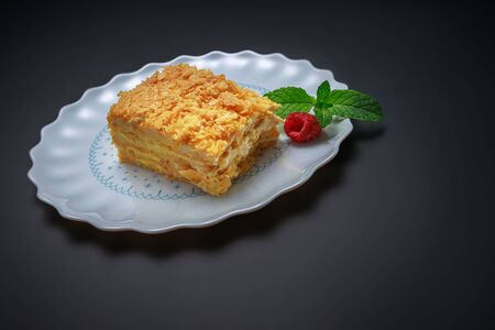 Cake Napoleon with vanilla milk cream on a stone plate isolated over black background