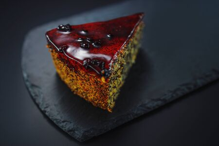 Cake with fruity cream and pistachio decorated with nuts, isolated on black stone.
