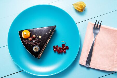 Chocolate cake with decoration and fruits wooden blue background. Reklamní fotografie