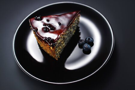 Cake with berry fruits, chia cereals and nuts isolated in a plate on black background Reklamní fotografie