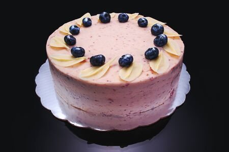 Cake chocolate with yogurt cream and blueberries fruits isolated on black background.