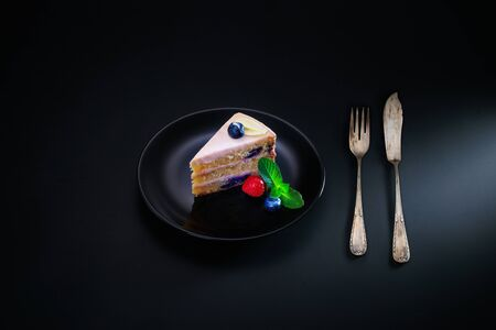 Cake chocolate with yogurt cream and blueberries fruits isolated on black background