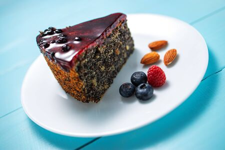 Cake with berry fruits, chia cereals and nuts isolated over wooden background.