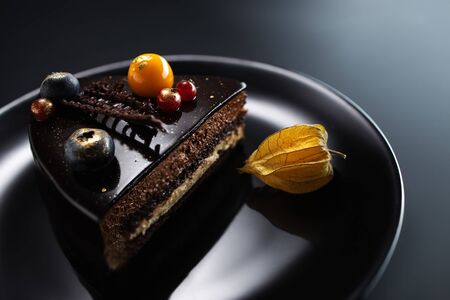 Chocolate cake with decoration and fruits on black background