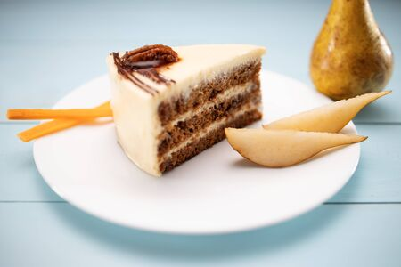 Cake piece with chocolate, milk cream, carrots and nuts isolated on a blue plate