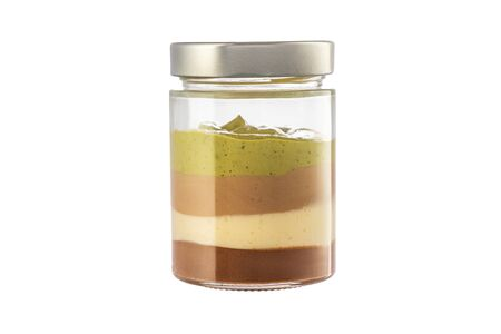 Milk creamy dessert in jar with nuts, chocolate and cacao beans isolated on white background. Reklamní fotografie