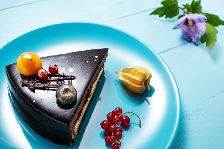 Chocolate cake with decoration and fruits on blue wooden background. Reklamní fotografie