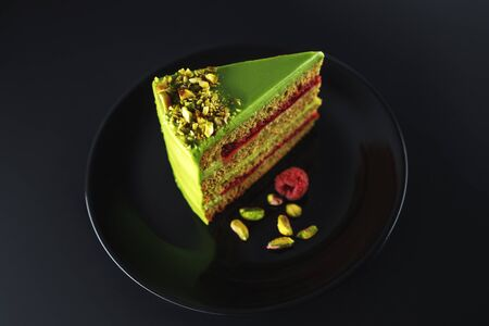 Cake with fruity cream and pistachio decorated with nuts, isolated on black background. Reklamní fotografie