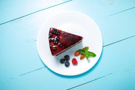 Cake with berry fruits, chia cereals and nuts isolated wooden background