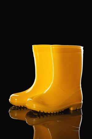Yellow Rubber Rain Boots for kids isolated on black background Reklamní fotografie