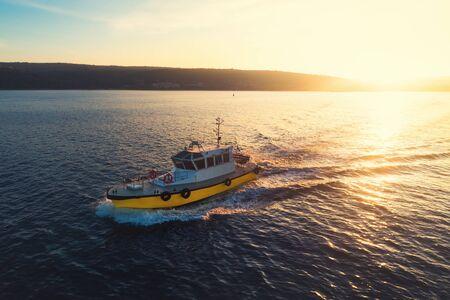 Patrol boat sailing at sunset in shining golden sea water.