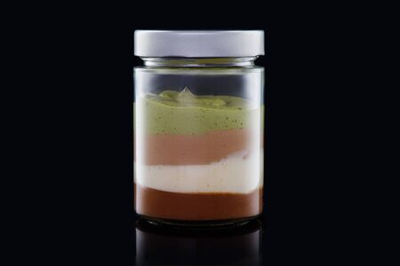 Milk creamy dessert in jar with nuts and chocolate and cacao beans isolated on black
