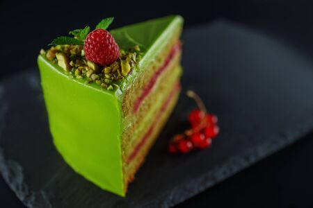 Cake with fruity cream and pistachio decorated with nuts, isolated on wooden background.