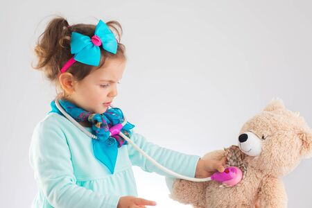 Cute kid girl playing doctor with plush toy at home.