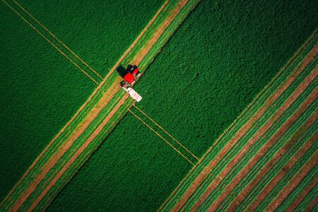 Red tractor mowing green field. Archivio Fotografico