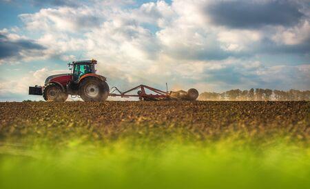 Landwirt im Traktor, der Land mit Saatbettgrubber vorbereitet