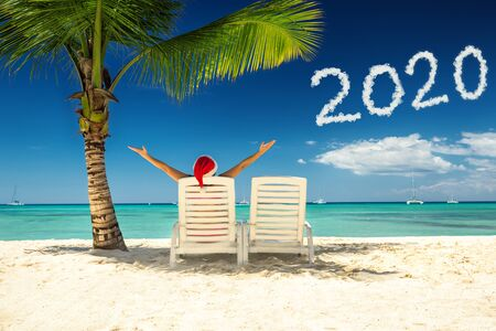 Woman in santa's hat relaxing on tropical beach Imagens