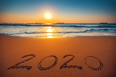 Happy New Year 2020 concept, lettering on the beach. Sea sunrise. Stock Photo