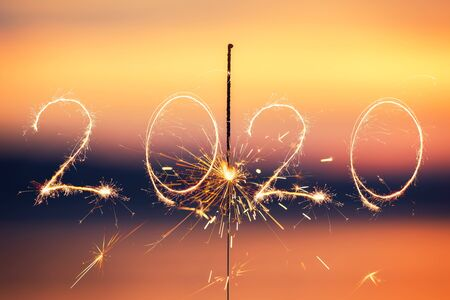 Bengal light on the sunset background, New Year with sparklers sparks on a sunset background. Zdjęcie Seryjne