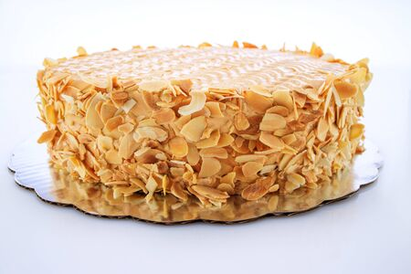 Cake with peanuts, walnuts, chocolate and caramel cream isolated on white background.