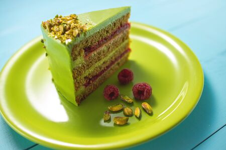 Cake with fruity cream and pistachio decorated with nuts, isolated in a green plate