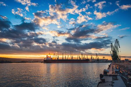 Colorful sunset over sea port and industrial cranes, Varna, Bulgaria Stock Photo