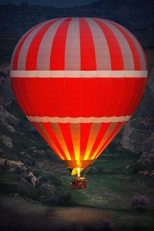 Hot air balloon flying over the valley at Cappadocia, Turkey.