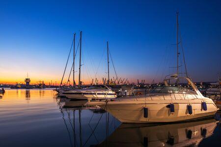 Yacht port and beautiful sunset over Varna, Bulgaria. Sailboat harbor, many beautiful moored sail yachts in the sea.