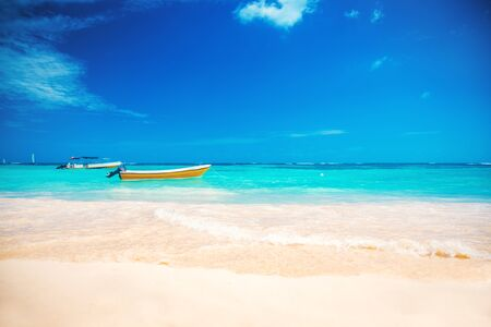 Beautiful carribean sea and boat on the shore, panoramic view from the beach