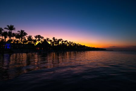 Tropical island at night. Palm trees silhouettes and lights on resort beach. Stok Fotoğraf