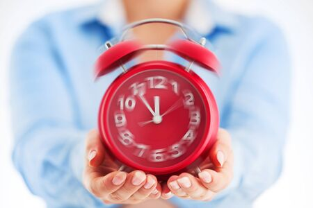 Business time concept. Woman holding red alarm clock in his hands close up. Banco de Imagens - 150647344