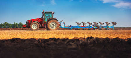 Tractor plowing the fields , agricultural landscape, panoramic view