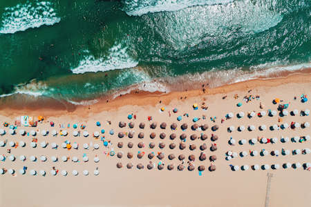 Aerial top view on the beach. Umbrellas, sand and sea waves Stock Photo