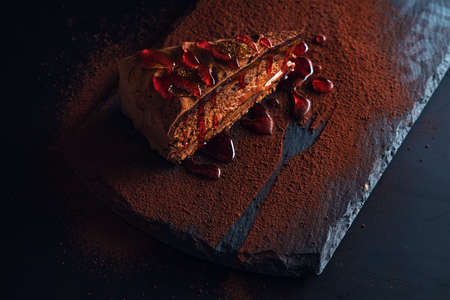 Piece of chocolate homemade cake with nuts and apricot jelly in a stone plate Stok Fotoğraf