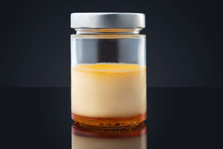 Cream caramel in a jar isolated on black background