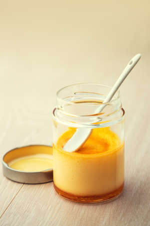 Cream caramel in a jar isolated on wooden background