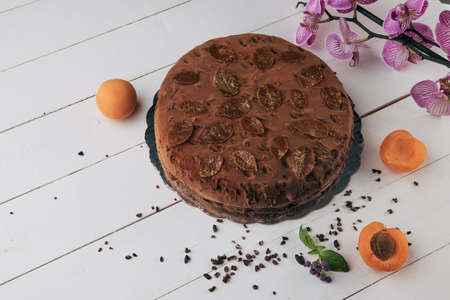 Chocolate homemade cake with nuts and apricot jelly on wooden background