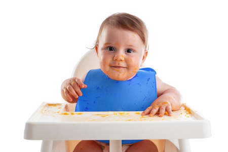 Cheerful baby child eats food itself with hands. Portrait of happy dirty kid boy in high chair and messy  around.