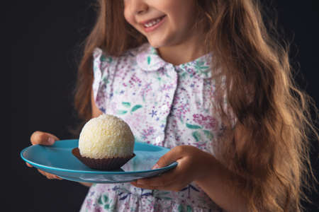 Beautiful little girl surprised from a tasty big chocolate coconut candy as a ball. Kid ready to eat cake.