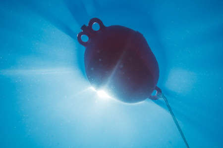 Underwater light creates a beautiful veils, consisting of sunlight. Underwater ocean waves and buoy float . Stok Fotoğraf