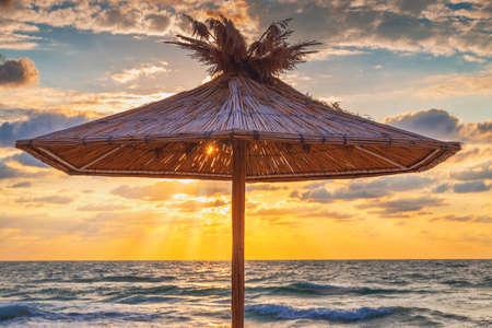 Straw umbrella on tropical sea beach Reklamní fotografie