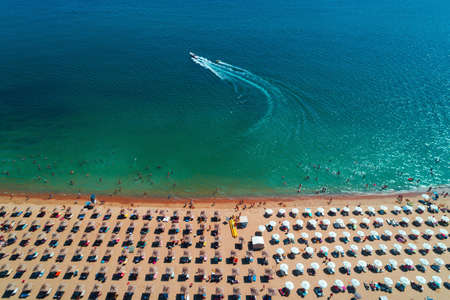 Aerial top view of sea, beach, sand, umbrellas and water sports activity. Summer seascape.